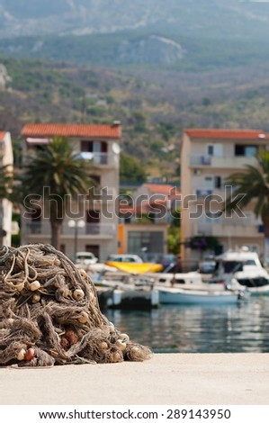 Pile of fishing nets with floats on a quay with blurred boats on background. Podgora, Croatia. Vertical photo - stock photo