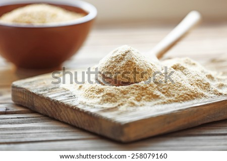 Pile of flour on cutting board with bowl and spoon on wooden background - stock photo
