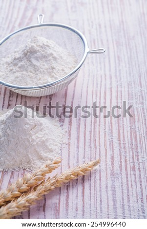 pile of flour wheat ears and sieve on vintage desk food and drink concept  - stock photo