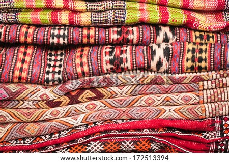 Pile of folded kilim and wool rugs as a background - stock photo