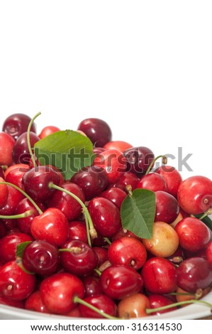 PILE OF FRESH CHERRIES OVER WHITE BACKGROUND.