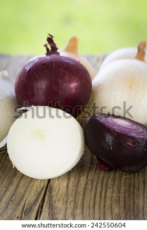 Pile of fresh cleaned red and white onions and a wooden kitchen table, whole and sliced, ready to be used as a pungent flavoring and ingredient in cooking and salads - stock photo