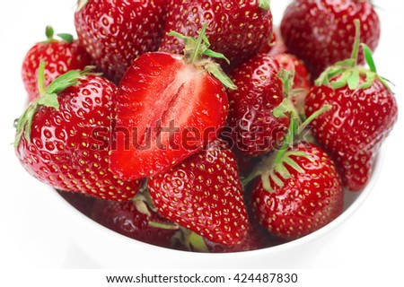 Pile of fresh ripe whole and cut strawberries in white bowl close-up. Top view. - stock photo