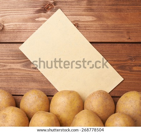 Pile of fresh washed potatoes lying against the copyspace brown piece of paper, composition over the wooden table's surface - stock photo