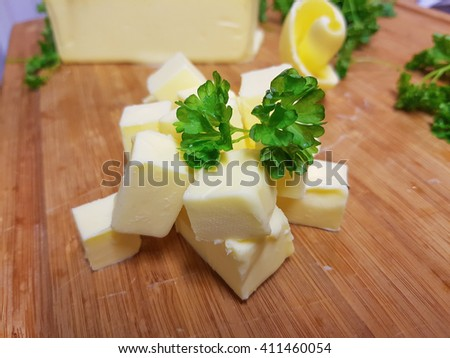 Pile of fresh, yellow butter cubes, on a wooden cutting board