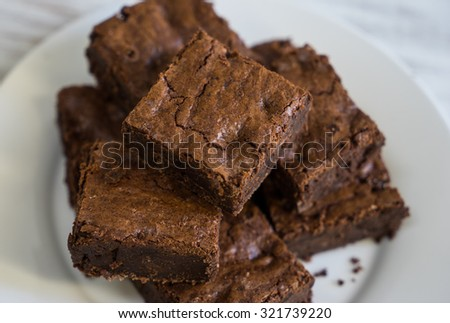 Pile of freshly baked brownies on white plate with crumbs on side sitting on vintage white board - stock photo