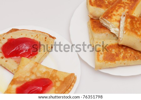 Pile of fritters with cottage cheese and pancakes with red currant jelly
