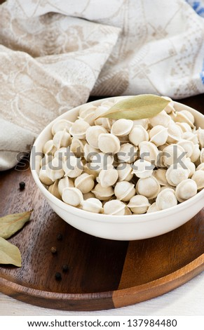 Pile of frozen mini pelmeni on a bowl, selective focus - stock photo