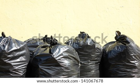 Pile of full black garbage bags outdoor - stock photo