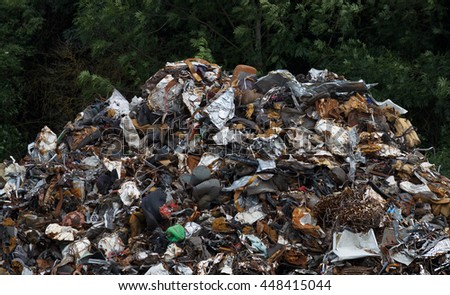 Pile of garbage, forest in the background. - stock photo
