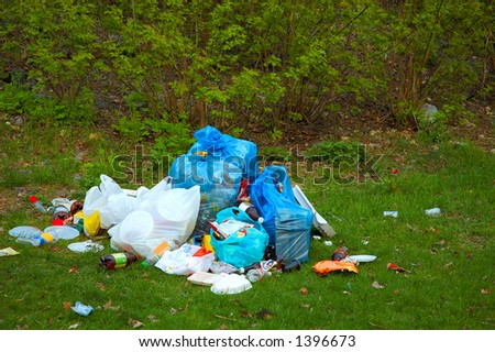 Pile of garbage on green grass in the nature environment problems