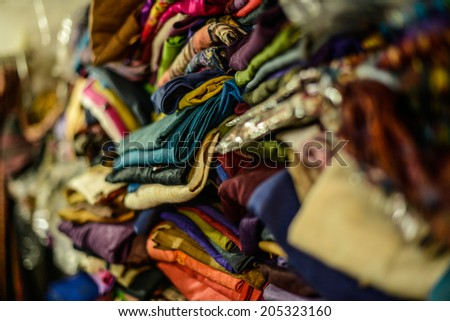Pile of gentle folded shawls (scarfs) at the market, India - stock photo