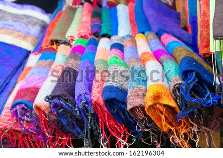 Pile of gentle folded shawls (scarfs) at the market, Pokhara, Nepal. - stock photo
