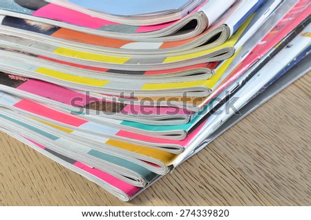pile of glossy colored fashion magazines on hardwood floor