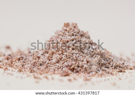 Pile of grated/ground Nutmeg on light background