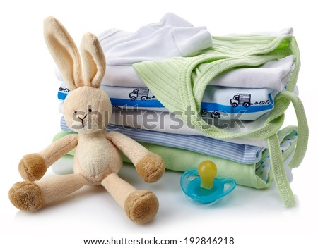 Pile of green and blue baby clothes, pacifier and toy isolated on white background - stock photo