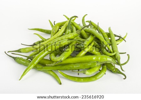 Pile of green chillies on a white background - stock photo