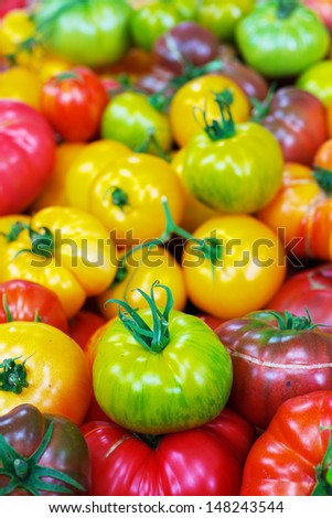 Pile of Green, Yellow, and Red Heritage Tomatoes at the farmers market - stock photo