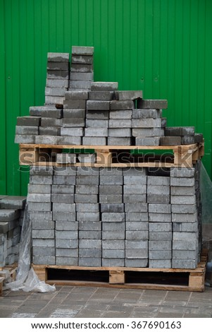 pile of grey bricks, over the green fence