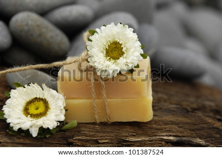 Pile of grey stones and pink flower with handmade soap on driftwood