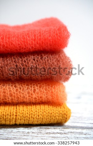 Pile of hand knit folded clothes in autumn colors
