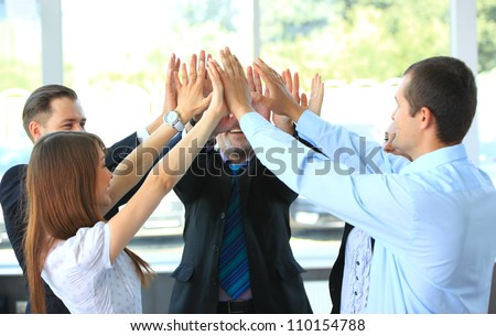 Pile of hands - Successful business team celebrating their success with a high five - stock photo