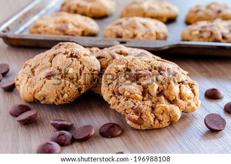 Pile of homemade chocolate chip cookies sitting in front of baking pan filled with cookies - stock photo