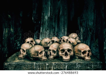 Pile of human skulls on stone table for sacrifice with golden and candle wax