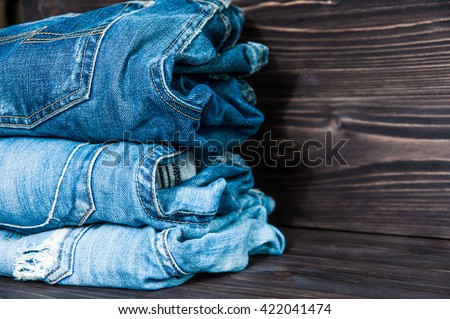 Pile of  jeans clothes on wooden background.  - stock photo