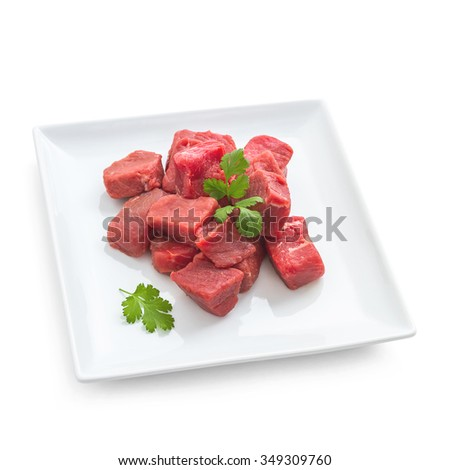 Pile of juicy beef cubes on plate, isolated top view - stock photo