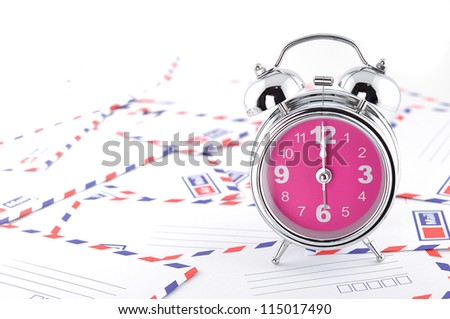 Pile of letter cards and clock alarm - stock photo