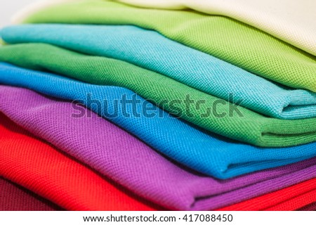 Pile of luxurious fine material 100% cotton polo shirts in various colors - stock photo