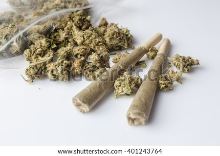 Pile of medical cannabis dried buds scattered from nylon package and two marijuana joints on white background from side - stock photo