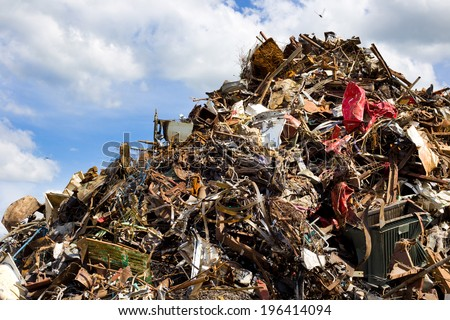 Pile of metal waste for recycling, blue sky and white clouds in background - stock photo