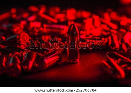 Pile of 9mm ammunition under menacing red light. - stock photo
