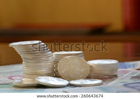Pile of money and stacked coins international for business and finance sterling silver walking liberty - stock photo