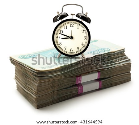 Pile of money in wrapper and alarm clock - stock photo