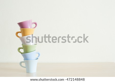 Pile of multicolor coffee cups on clear background look like tower.