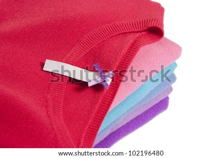 Pile of multicolored knitted clothes with blank label macro on white - stock photo