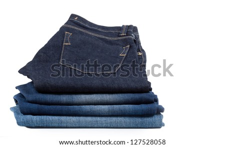 Pile of neatly folded denim jeans with the top pair lifted to display the pocket isolated on white - stock photo