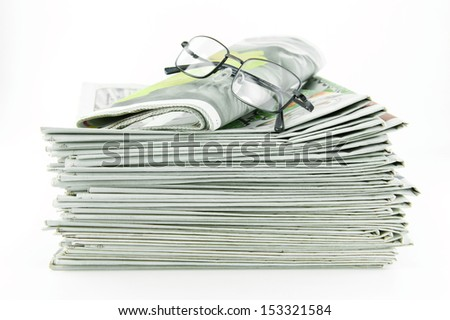pile of newspaper with glasses isolated on white background
