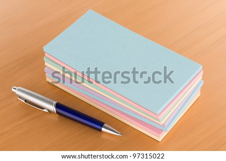 Pile of Note Pads with Pen on Table