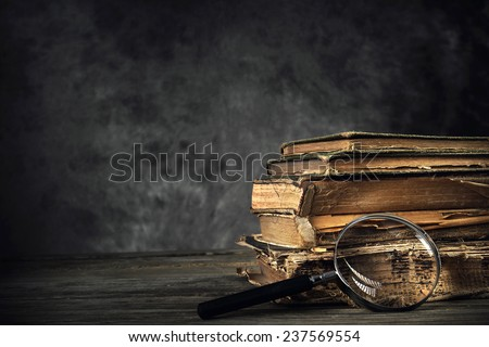 Pile of old antique and yellowed books with a magnifying glass in a dark, grungy library - stock photo