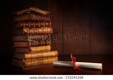 Pile of old books and diploma on desk - stock photo