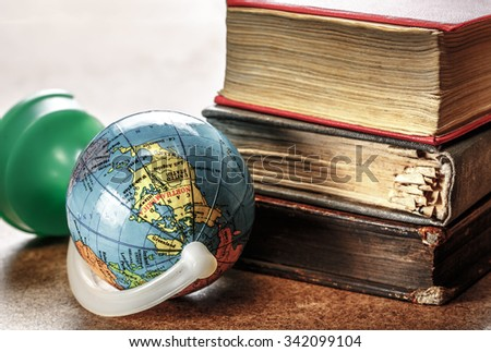 Pile of old books and globe in closeup - stock photo