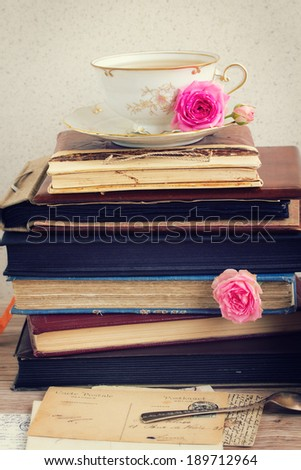 pile of old books and mail with antique cup of tea - stock photo