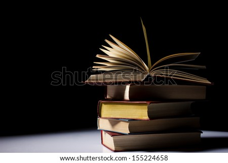 pile of old books on light table, one book opened,  black background - stock photo