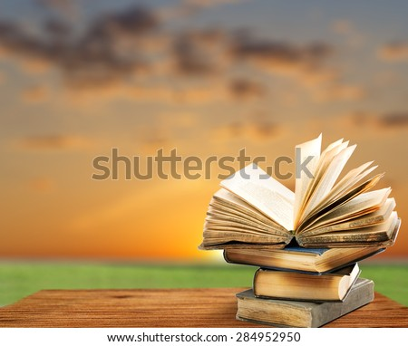 Pile of old books on sky background - stock photo