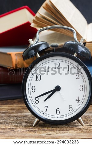 pile of  old books with antique alarm clock  on wooden shelf