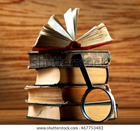 Pile of old books with magnifying glass on wooden background
